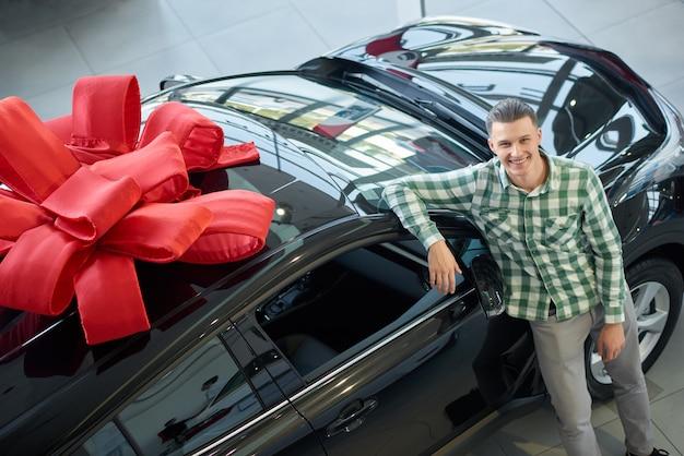 Atrakcyjny facet stojący w pobliżu wielkiego czarnego samochodu z kokardą na górze.