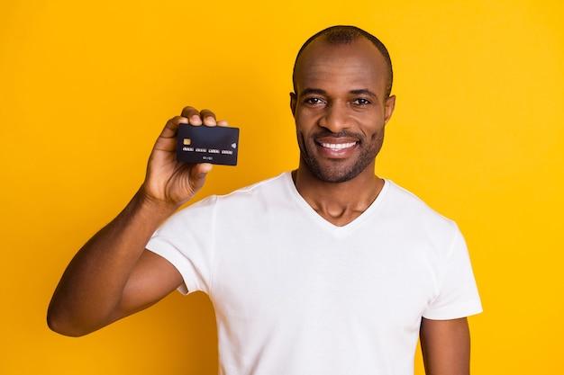 Atrakcyjny facet trzyma plastikową kartę kredytową