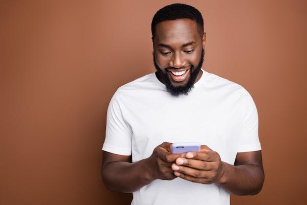 Atrakcyjny facet w ubranie pozuje na brązowej ścianie
