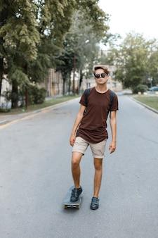 Atrakcyjny fajny młody hipster mężczyzna w okularach przeciwsłonecznych w stylowej koszulce w letnich szortach w trampkach na deskorolce w parku w ciepły letni dzień