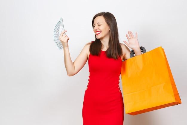 Atrakcyjny glamour modne młode brązowe włosy kobieta w czerwonej sukience gospodarstwa dolarów gotówki, multi kolorowe pakiety z zakupami po zakupach na białym tle. skopiuj miejsce na reklamę.