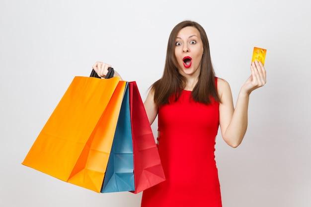 Atrakcyjny glamour modne młode brązowe włosy kobieta w czerwonej sukience trzymając kartę kredytową, multi kolorowe pakiety z zakupów po zakupach na białym tle. skopiuj miejsce na reklamę.