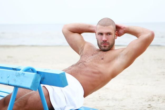 Atrakcyjny i szczęśliwy mężczyzna na plaży