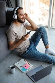 Atrakcyjny, inteligentny młody człowiek siedzący na podłodze w salonie, słuchający muzyki za pomocą bezprzewodowych słuchawek i telefonu komórkowego