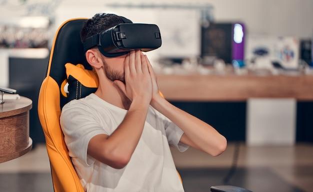 Atrakcyjny kaukaski brodaty mężczyzna próbuje technologii wirtualnej rzeczywistości, siedząc na krześle w tech store.