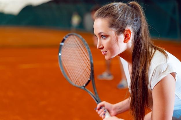 Atrakcyjny kobiety gracz w tenisa czekanie dla usługa przy salowym sądem