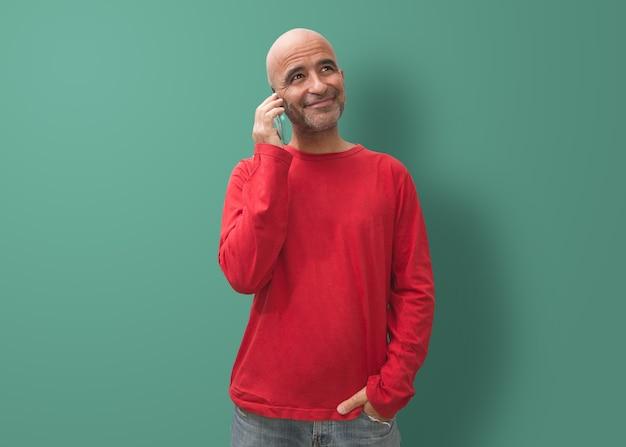 Atrakcyjny łysy mężczyzna manipulujący urządzeniem mobilnym