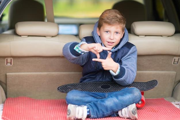 Atrakcyjny mały chłopiec siedzący w bagażniku samochodu, wykonujący gest ramki palcami, uśmiechający się do kamery