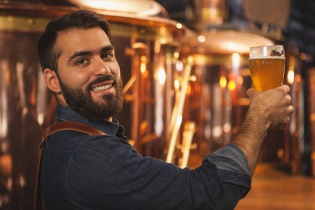 Atrakcyjny męski barman pozuje przy szklance pełnej smakowitego piwa