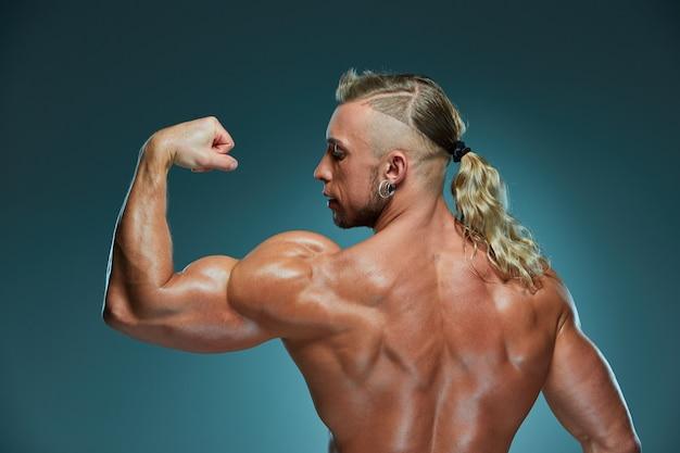 Atrakcyjny męski budowniczy pokazuje mięśnie