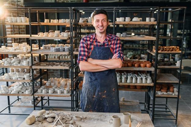 Atrakcyjny męski garncarz ze skrzyżowanymi rękami w ceramice.
