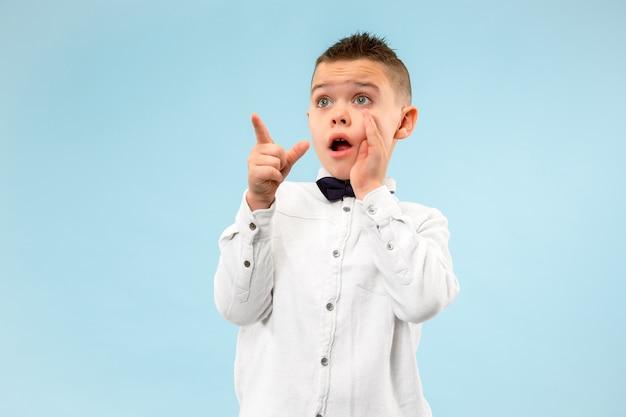 Atrakcyjny męski portret w połowie długości z przodu na niebieskim tle studio. młody emocjonalny zaskoczony chłopiec nastolatek stojąc z otwartymi ustami.