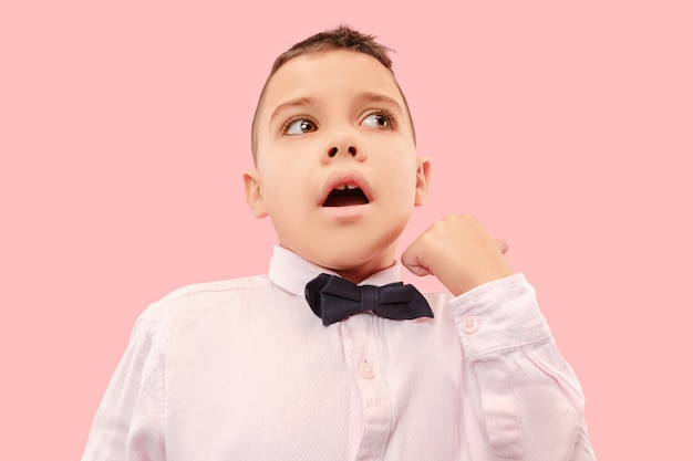 Atrakcyjny męski portret w połowie długości z przodu na różowym tle studio. młody emocjonalny zaskoczony chłopiec nastolatek stojąc z otwartymi ustami.