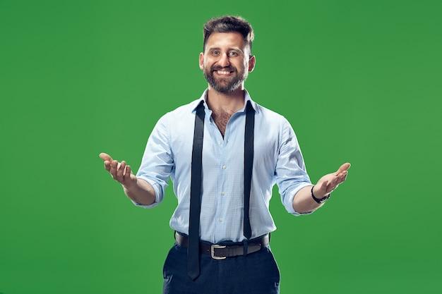 Atrakcyjny męski portret w połowie długości z przodu na zielonym tle studio.