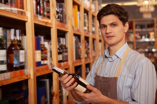 Atrakcyjny męski producent wina pewnie patrząc w kamerę, pracujący w swoim sklepie