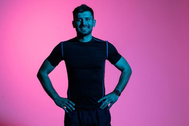 Atrakcyjny mężczyzna fitness w odzieży sportowej na białym tle na różowym jasnym tle