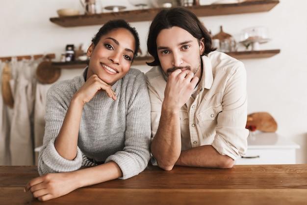 Atrakcyjny mężczyzna i całkiem uśmiechnięta african american kobieta szczęśliwie opierając się na stole
