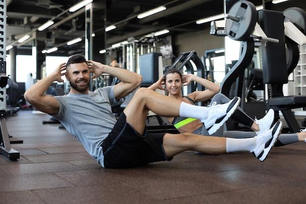 Atrakcyjny mężczyzna i kobieta pracująca w parach wykonujących siedzieć ups w siłowni.