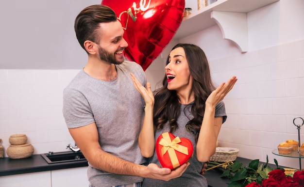 Atrakcyjny mężczyzna i ładna kobieta w domowych ubraniach stoją w kuchni i uśmiechają się, wręczając sobie prezenty w walentynki.