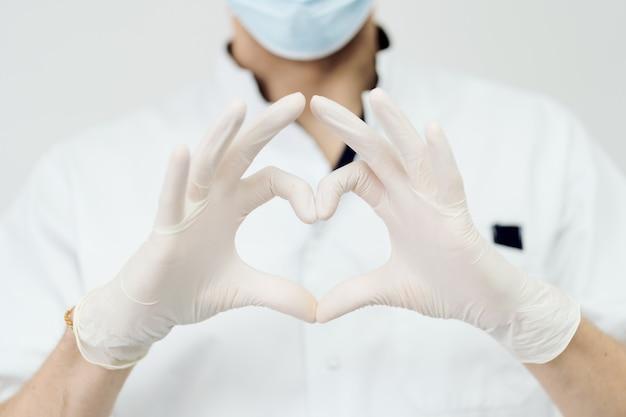Atrakcyjny mężczyzna lekarz pokazuje znak serca z rękami na białej ścianie