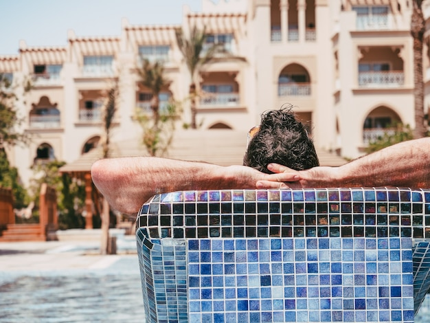 Atrakcyjny mężczyzna leżący na leżaku na tle basenu kąpielowego