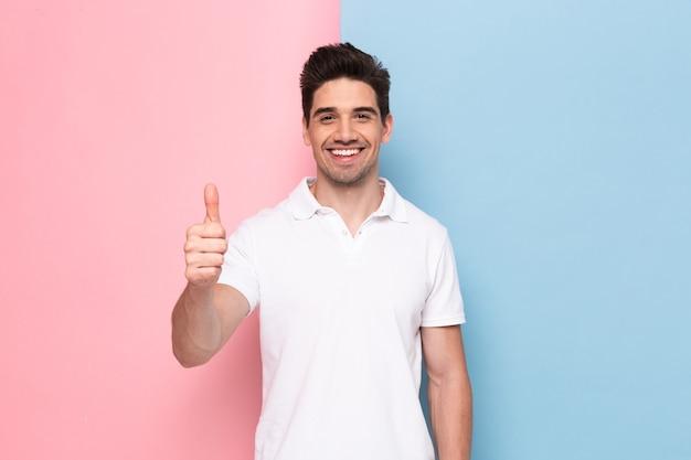 Atrakcyjny mężczyzna o zarost pokazujący kciuk z radosnym uśmiechem, odizolowane na kolorowej ścianie