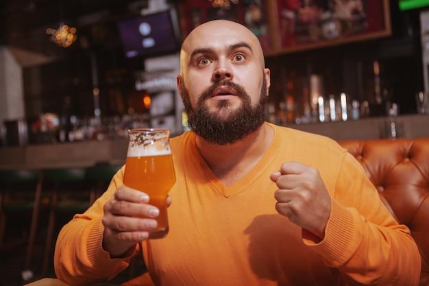 Atrakcyjny mężczyzna ogląda mecz w barze sportowym, trzymając w ręku piwo