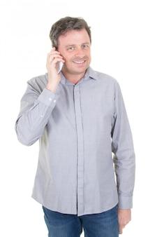 Atrakcyjny mężczyzna opowiada na telefonie i patrzeje daleko od odizolowywający