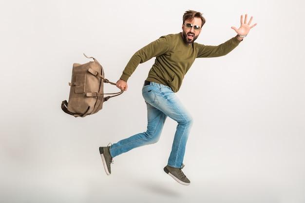 Atrakcyjny mężczyzna podróżnik na białym tle spóźniony z workiem śmieszne wypowiedzi