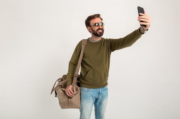 Atrakcyjny mężczyzna podróżnik z torbą na białym tle, biorąc zdjęcie selfie