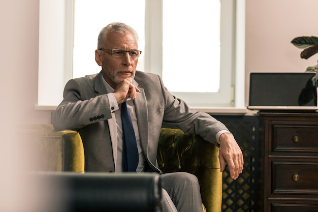 Atrakcyjny mężczyzna. portret przystojnego siwego mężczyzny siedzącego w oliwkowozielonym fotelu, patrzącego nieruchomo w dal