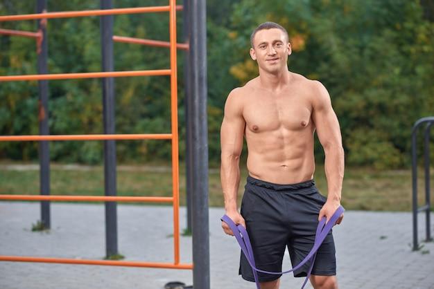 Atrakcyjny mężczyzna pozuje podczas treningu z zespołami oporu.