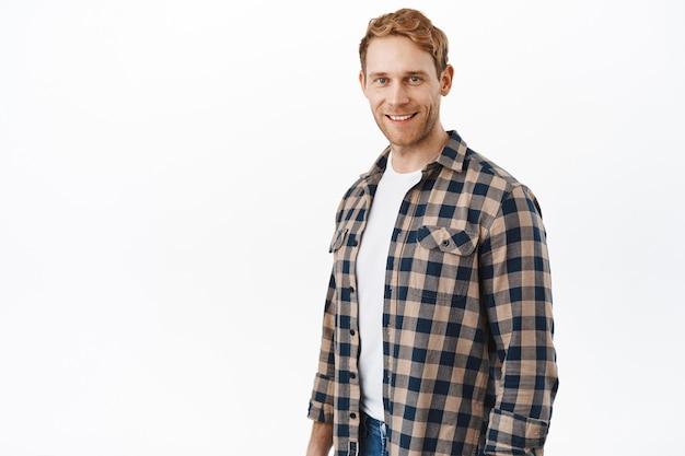 Atrakcyjny mężczyzna rasy kaukaskiej z rudymi włosami i niebieskimi oczami, wyglądający na szczęśliwego z przodu, uśmiechnięty i stojący swobodnie na białej ścianie