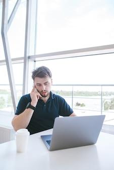Atrakcyjny mężczyzna siedzi przy stole w oknie coworking, korzysta z laptopa i rozmawia przez telefon