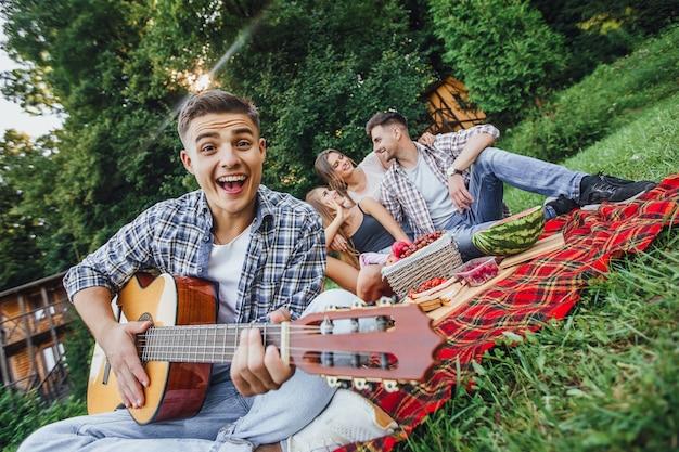 Atrakcyjny mężczyzna siedzi w trawie i gra na gitarze, ma piknik z trzema przyjaciółmi