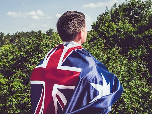 Atrakcyjny mężczyzna trzyma flagę australijską. święto narodowe