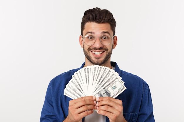 Atrakcyjny mężczyzna trzyma gotówkowego pieniądze w jeden ręce, na odosobnionym bielu