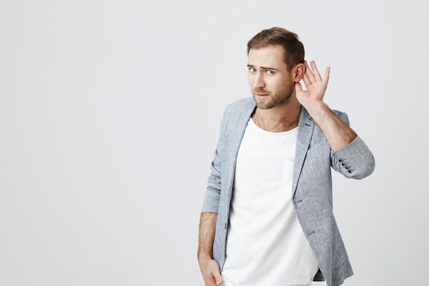 Atrakcyjny mężczyzna trzyma rękę w pobliżu ucha prosząc o powtórzenie, próbując usłyszeć