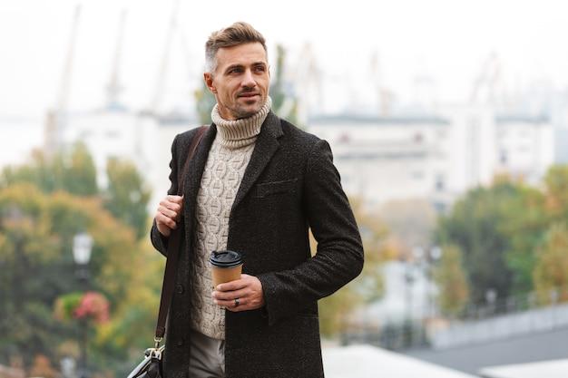 Atrakcyjny mężczyzna ubrany w kurtkę spacery na świeżym powietrzu, trzymając kubek kawy na wynos