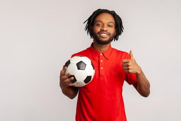 Atrakcyjny mężczyzna uśmiechający się, trzymając w ręku piłkę nożną i pokazując kciuk do góry, patrząc na kamery.
