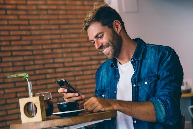 Atrakcyjny mężczyzna używa telefon komórkowego ma kawę