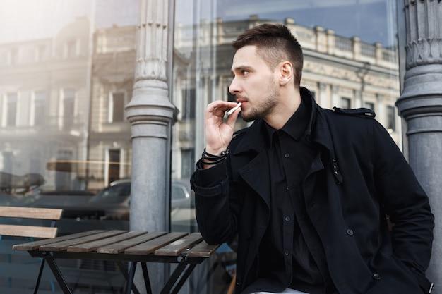 Atrakcyjny mężczyzna w czarnych ubraniach usiadł, żeby wypić papierosa.