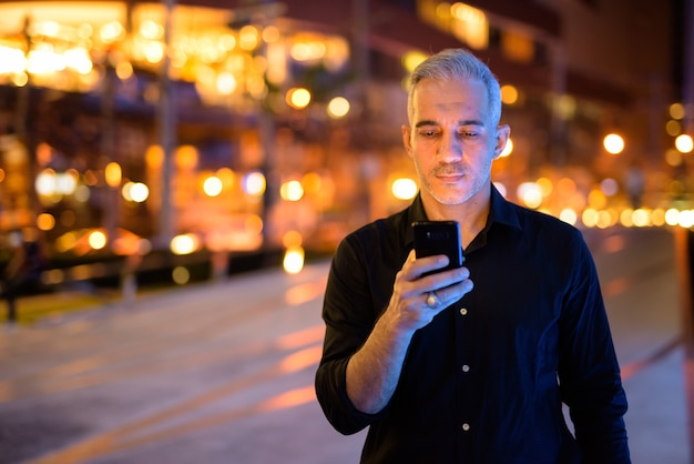 Atrakcyjny mężczyzna w nocy na ulicach przy użyciu telefonu komórkowego