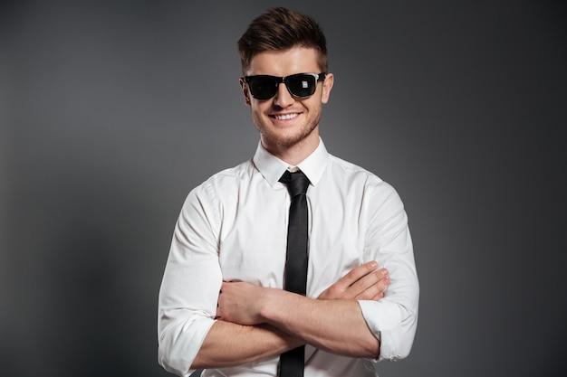 Atrakcyjny mężczyzna w okularach przeciwsłonecznych i odzieży stojącej z założonymi rękami