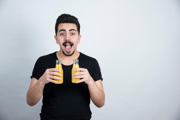 Atrakcyjny mężczyzna w okularach przeciwsłonecznych, trzymając szklane butelki z sokiem pomarańczowym.