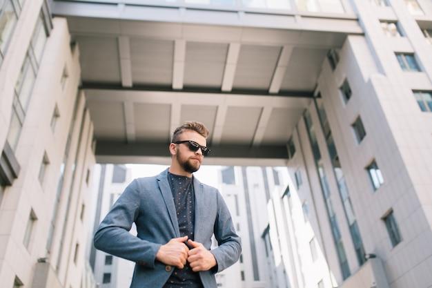 Atrakcyjny mężczyzna w okularach stoi na zewnątrz