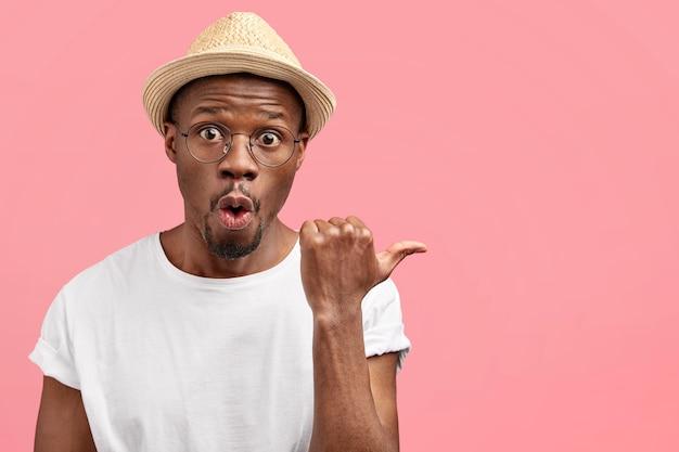 Atrakcyjny mężczyzna w średnim wieku robotnik rolny w zwykłym ubraniu i kapeluszu, wskazuje na bok kciukiem, pokazuje puste miejsce na różowej ścianie