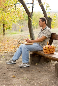 Atrakcyjny mężczyzna w średnim wieku siedzi na rustykalnej drewnianej ławce na świeżym powietrzu, jedząc jabłka z koszem pełnym świeżych owoców u boku