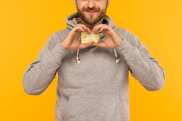 Atrakcyjny mężczyzna w szarej bluzie z kapturem trzyma w rękach kartę kredytową na żółtym tle - obraz