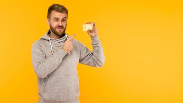 Atrakcyjny mężczyzna w szarej bluzie z kapturem wskazuje palcem na kartę kredytową, która trzyma w ręku na żółtym tle - obraz